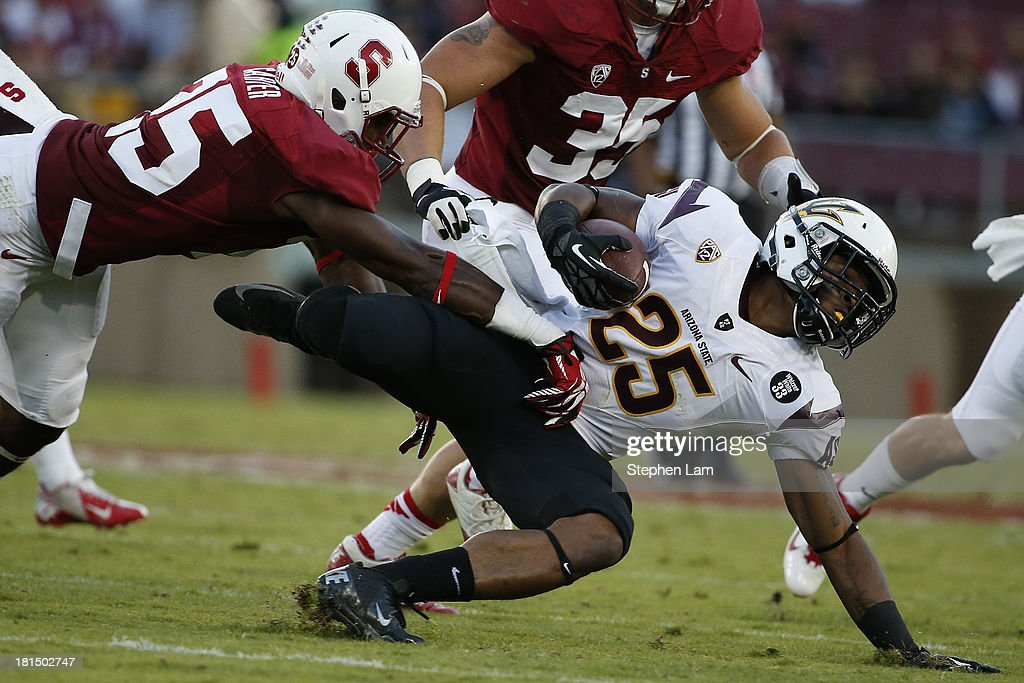 Running back Deantre Lewis #25 of the Arizona State Sun Devils falls as cornerback Alex Carter #25 (L) of the the Stanford Cardinal tackles during the third quarter at Stanford Stadium on September 21, 2013 in Stanford, California. The Cardinals defeated the Sun Devils 42-28.