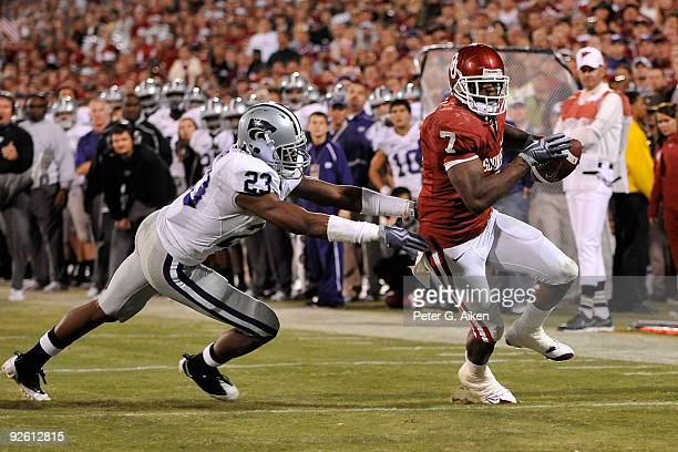 Running back DeMarco Murray of the Oklahoma Sooners slips past free safety Emmanuel Lamur of the Kansas State Wildcats for a second half touchdown on...