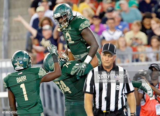 Running back D'Ernest Johnson of the South Florida Bulls celebrates with teammates wide receiver Chris Barr and offensive lineman Cameron Ruff after...