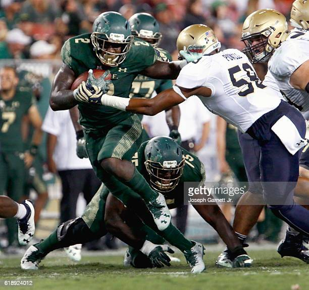 Running back D'Ernest Johnson of the South Florida Bulls pushes away defensive tackle Josiah Powell of the Navy Midshipmen during the second quarter...