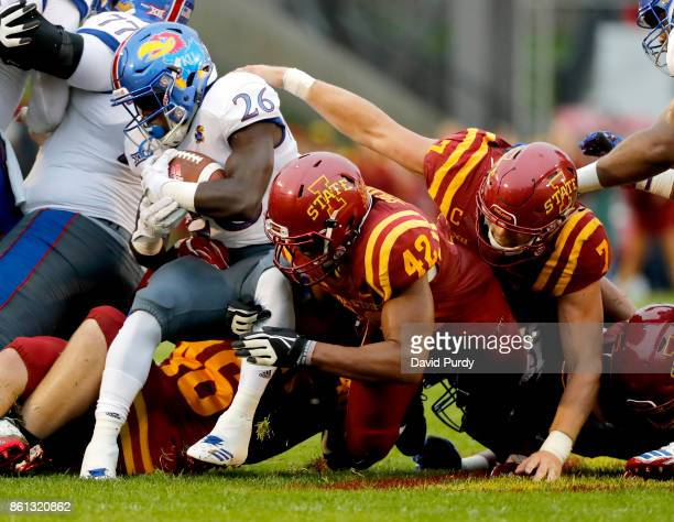 Running back Deron Thompson of the Kansas Jayhawks is tackled by linebacker Marcel Spears Jr #42 and linebacker Joel Lanning of the Iowa State...