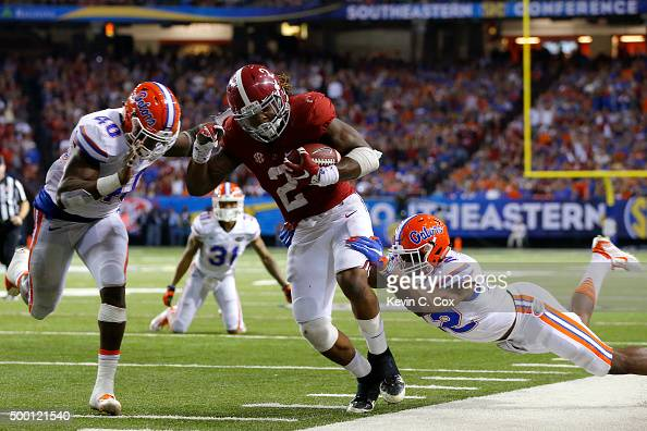 Running back Derrick Henry of the Alabama Crimson Tide carries the ball against linebacker Jarrad Davis of the Florida Gators and defensive back...