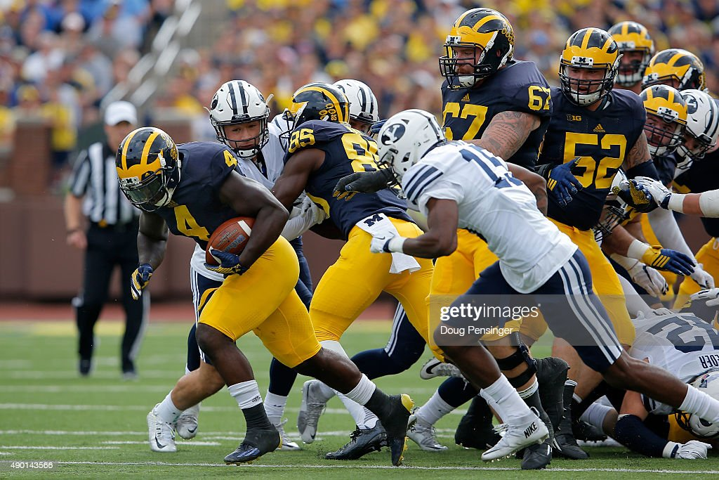 Running back De'Veon Smith of the Michigan Wolverines breaks loose from the line of scrimmage to run 60 yards for a touchdown against the Brigham...