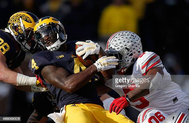Running back De'Veon Smith of the Michigan Wolverines is tackled by Raekwon McMillan of the Ohio State Buckeyes in the fourth quarter at Michigan...