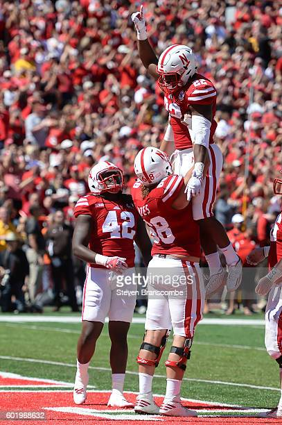Running back Devine Ozigbo gets lifted by offensive lineman Nick Gates as tight end Trey Foster of the Nebraska Cornhuskers looks on after scoring...