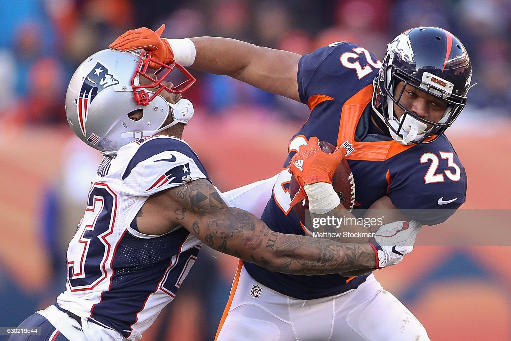 running back Devontae Booker #23 of the Denver Broncos gives a stiff arm to strong safety Patrick Chung #23 of the New England Patriots in the second quarter of a game at Sports Authority Field at Mile High on December 18, 2016 in Denver, Colorado.