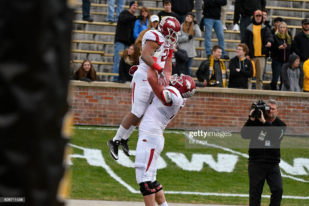 Running back Devwah Whaley #21 of the Arkansas Razorbacks celebrates his touchdown with offensive lineman Dan Skipper #70 of the Arkansas Razorbacks against the Missouri Tigers at Memorial Stadium on November 25, 2016 in Columbia, Missouri.