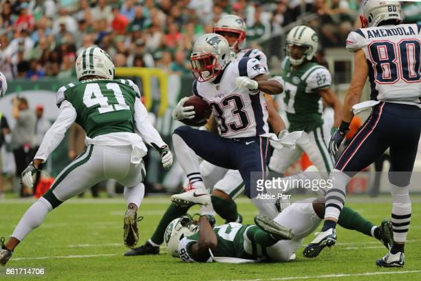 running back Dion Lewis of the New England Patriots jumps over free safety Marcus Maye of the New York Jets as he runs the ball during the second...