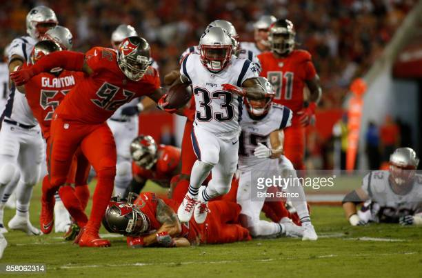 Running back Dion Lewis of the New England Patriots slips tackles from free safety Chris Conte of the Tampa Bay Buccaneers and defensive end William...