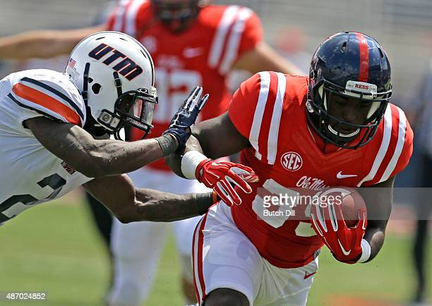 Running back DK Buford of the Mississippi Rebels is pushed out of bounds by defensive back Terrious Triplett of the Tennessee Martin Skyhawks during...
