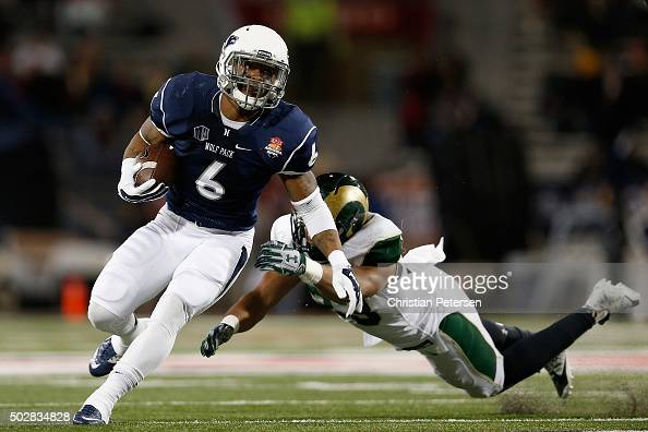 Running back Don Jackson of the Nevada Wolf Pack rushes the football past linebacker Kevin Davis of the Colorado State Rams during the second quarter...