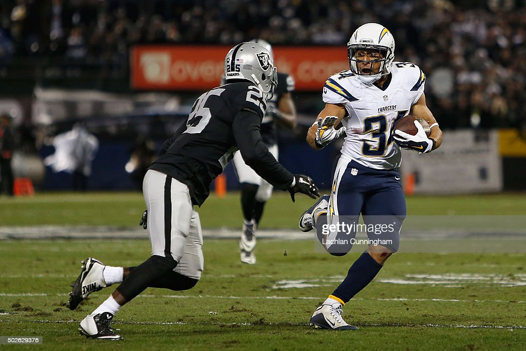 Running back Donald Brown of the San Diego Chargers looks to evade cornerback DJ Hayden of the Oakland Raiders in the first quarter at Oco Coliseum...