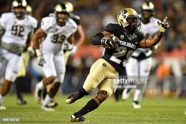 Running back Donovan Lee of the Colorado Buffaloes rushes for a second half first down against the Colorado State Rams at Sports Authority Field at...