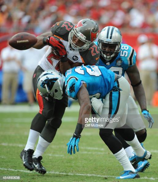 Running back Doug Martin of the Tampa Bay Buccaneers drops the ball after being hit by cornerback Bene Benwikere of the Carolina Panthers in the...