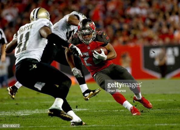 Running back Doug Martin of the Tampa Bay Buccaneers evades strong safety Roman Harper of the New Orleans Saints during a carry in the fourth quarter...