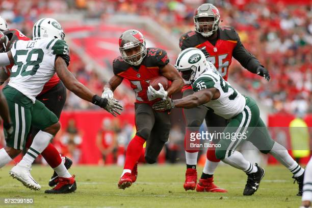 Running back Doug Martin of the Tampa Bay Buccaneers finds room to run between inside linebacker Darron Lee of the New York Jets and outside...
