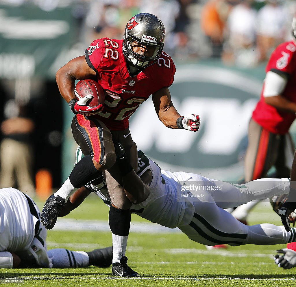 Running back Doug Martin #22 of the Tampa Bay Buccaneers is breaks away from the traps of linebacker DeMario Davis #56 of the New York Jets in the fourth quarter during a game at MetLife Stadium on September 8, 2013 in East Rutherford, New Jersey. The Jets defeated the Bucs 18-17.