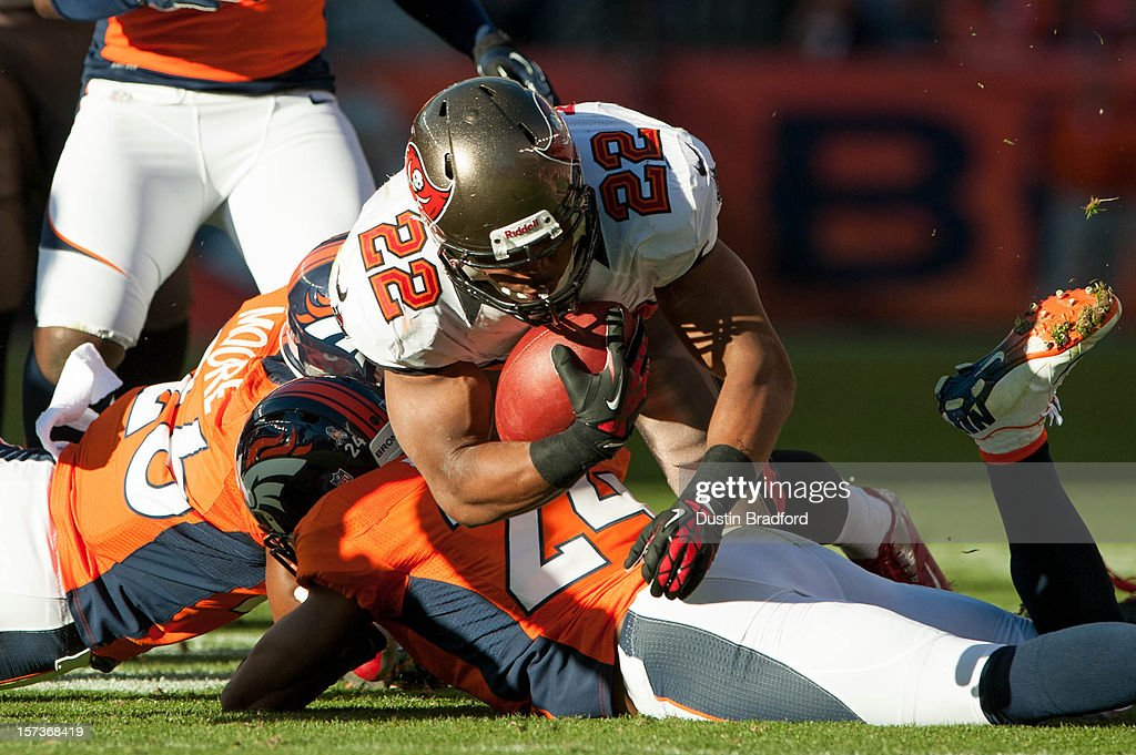 Running back Doug Martin #22 of the Tampa Bay Buccaneers is brought down by cornerback Champ Bailey #24 of the Denver Broncos during a game at Sports Authority Field Field at Mile High on December 2, 2012 in Denver, Colorado.
