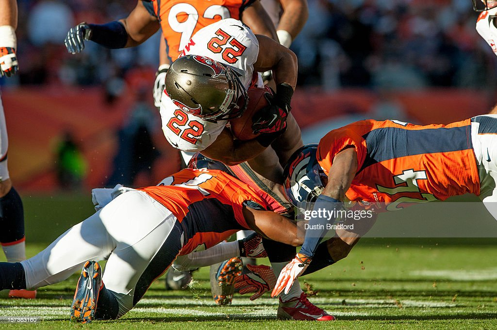 Running back Doug Martin #22 of the Tampa Bay Buccaneers is tackled by a pair of Denver Broncos as he rushes up the middle during a game at Sports Authority Field Field at Mile High on December 2, 2012 in Denver, Colorado.