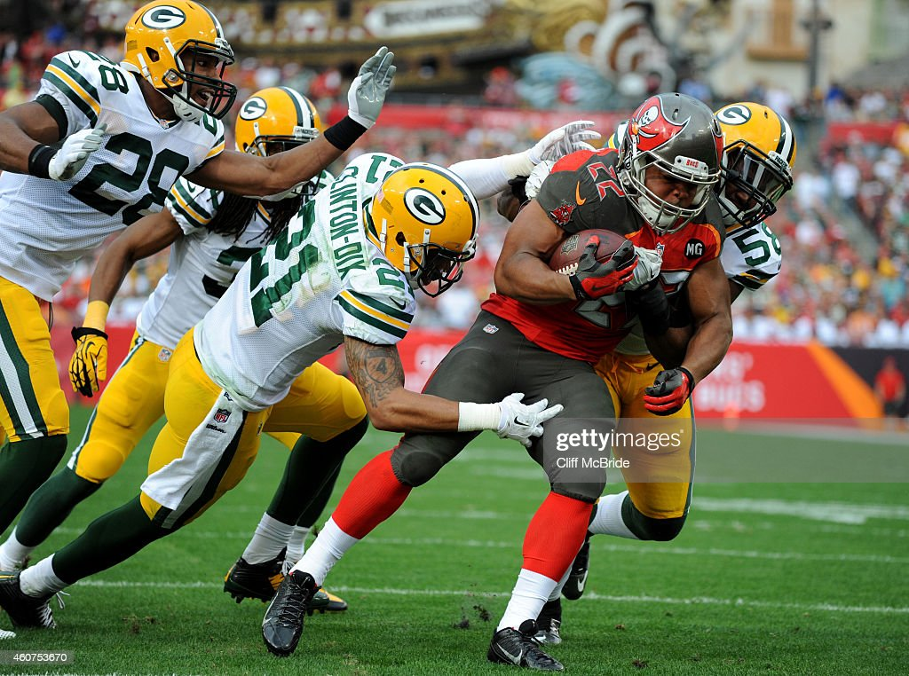 Running back Doug Martin #22 of the Tampa Bay Buccaneers is tackled by free safety Ha Ha Clinton-Dix #21 of the Green Bay Packers and inside linebacker Sam Barrington #58 of the Green Bay Packers in the third quarter at Raymond James Stadium on December 21, 2014 in Tampa, Florida.