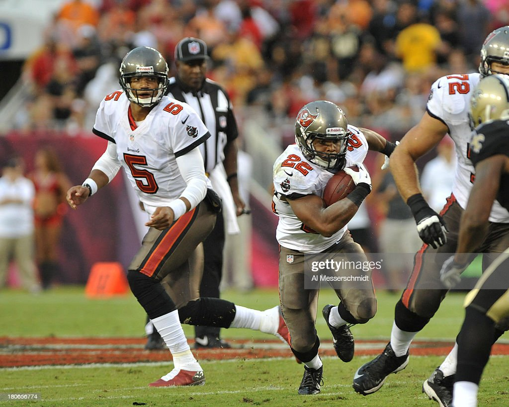 Running back Doug Martin #22 of the Tampa Bay Buccaneers takes a handoff from quarterback Josh Freeman #5 against the New Orleans Saints September 15, 2013 at Raymond James Stadium in Tampa, Florida.