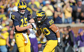 Running back Drake Johnson of the Michigan Wolverines scores on a one yard run and is congratuled by teammate Jake Rudock during the first quarter of...