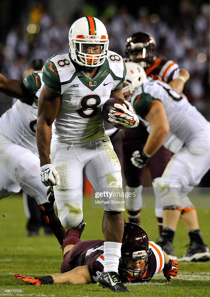 Running back <a gi-track='captionPersonalityLinkClicked' href=/galleries/search?phrase=Duke+Johnson+-+Jogador+de+futebol+americano&family=editorial&specificpeople=13981151 ng-click='$event.stopPropagation()'>Duke Johnson</a> #8 of the Miami Hurricanes breaks through a large hole to score a touchdown in the first half against the Virginia Tech Hokies at Lane Stadium on October 23, 2014 in Blacksburg, Virginia. Miami defeated Virginia Tech 30-6.