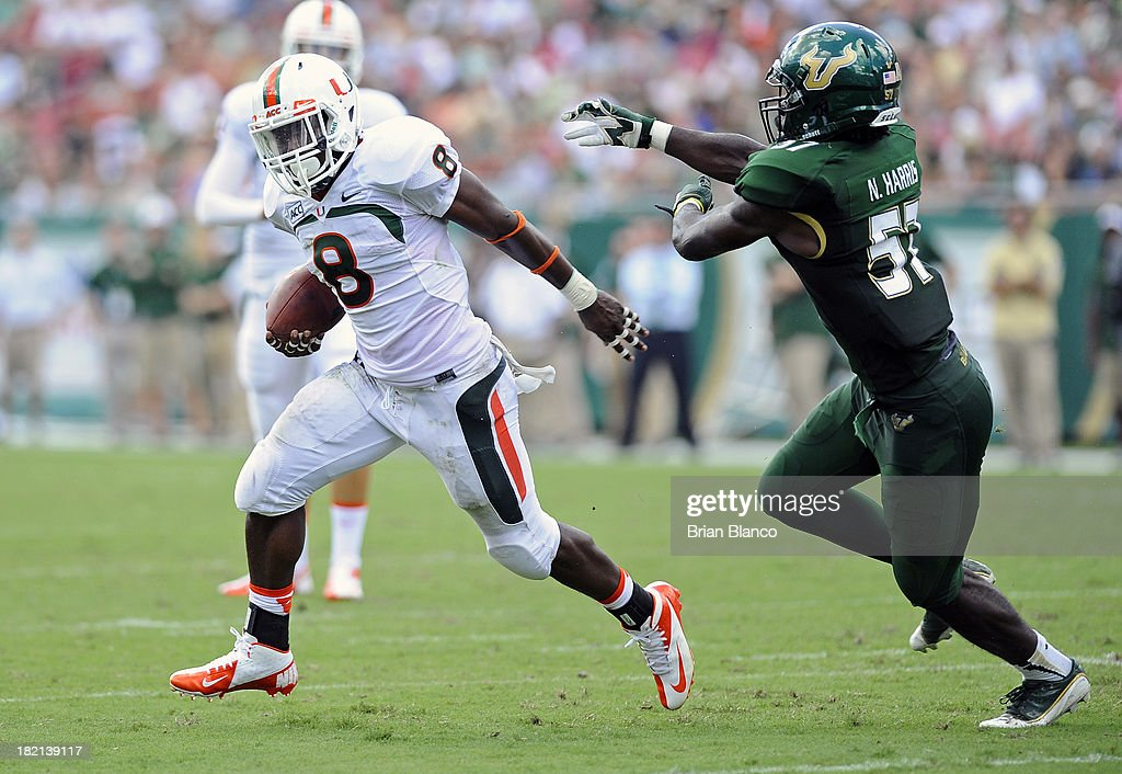 Running back Duke Johnson #8 of the Miami Hurricanes evades linebacker Nigel Harris #57 of the South Florida Bulls during a carry in the first quarter on September 28, 2013 at Raymond James Stadium in Tampa, Florida.