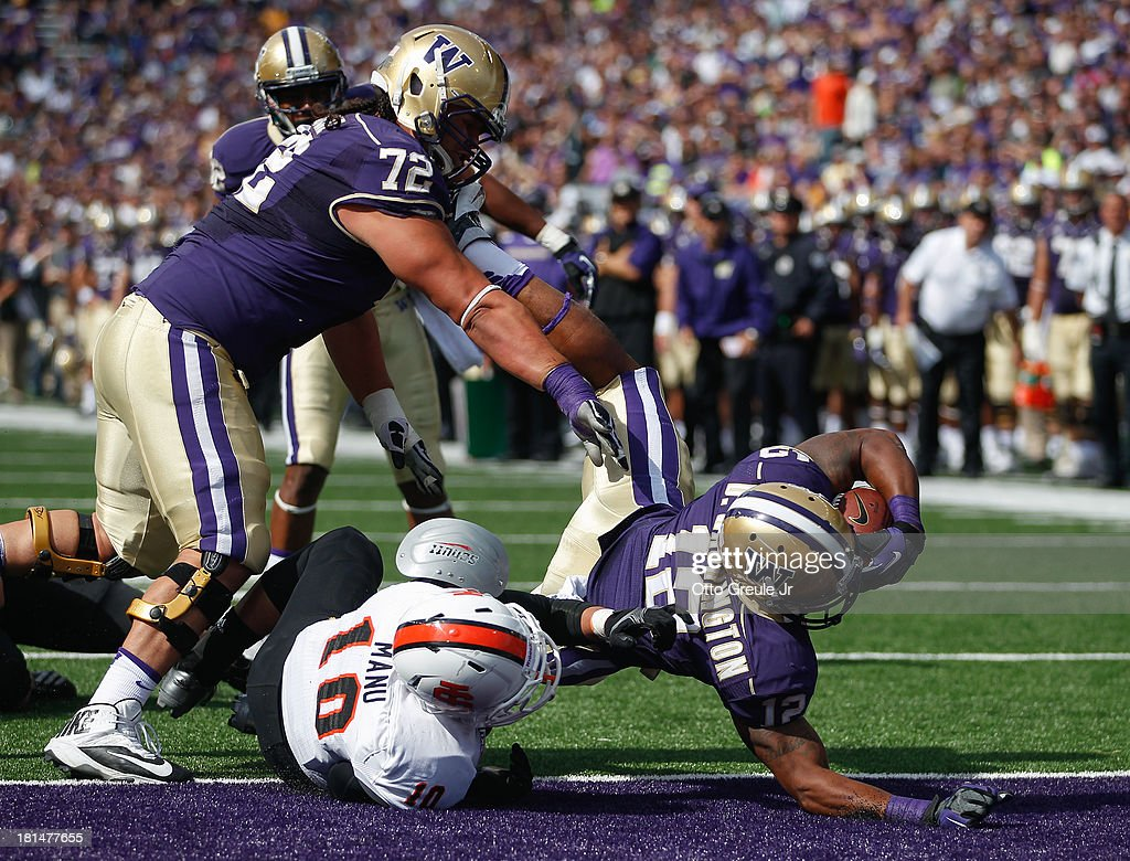 Running back Dwayne Washington #12 of the Washington Huskies crosses the goal line for a touchdown with the help of lineman Micah Hatchie #72 against Taison Manu #10 of the Idaho State Bengals on September 21, 2013 at Husky Stadium in Seattle, Washington. The Huskies defeated the Bengals 56-0.