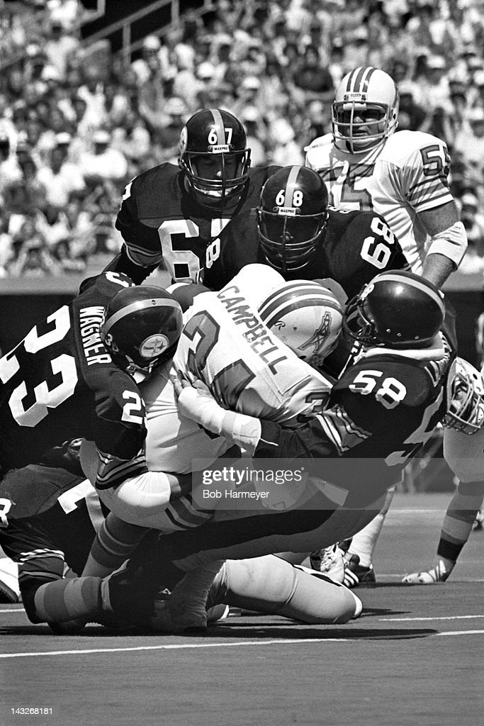 Running back <a gi-track='captionPersonalityLinkClicked' href=/galleries/search?phrase=Earl+Campbell&family=editorial&specificpeople=570909 ng-click='$event.stopPropagation()'>Earl Campbell</a> #34 of the Houston Oilers is stopped by linebacker <a gi-track='captionPersonalityLinkClicked' href=/galleries/search?phrase=Jack+Lambert&family=editorial&specificpeople=225108 ng-click='$event.stopPropagation()'>Jack Lambert</a> #58 and safety Mike Wagner #23 of the Pittsburgh Steelers on September 7, 1980, at Three Rivers Stadium in Pittsburgh, Pennsylvania.