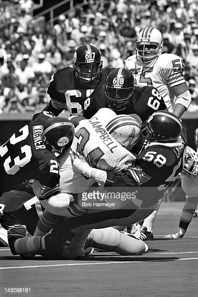 Running back Earl Campbell of the Houston Oilers is stopped by linebacker Jack Lambert and safety Mike Wagner of the Pittsburgh Steelers on September...