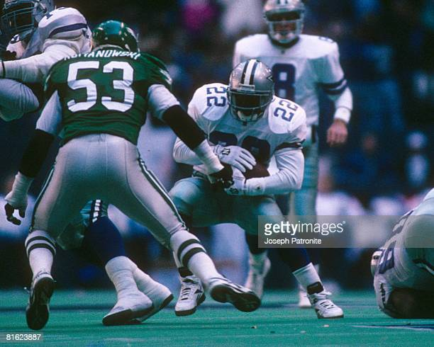 Running back Emmitt Smith of the Dallas Cowboys tries to elude linebacker Bill Romanowski of the Philadelphia Eagles at Texas Stadium in the 1995 NFC...