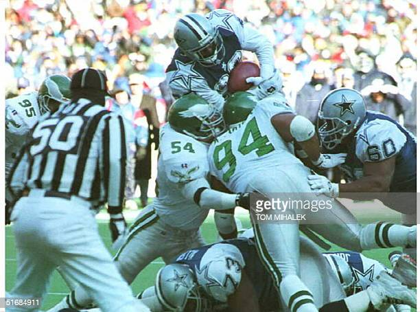 Running back Emmitt Smith of the Dallas Cowboys tries to go up and over to score but is stopped at the goal line by Philadelphia Eagles defenders...
