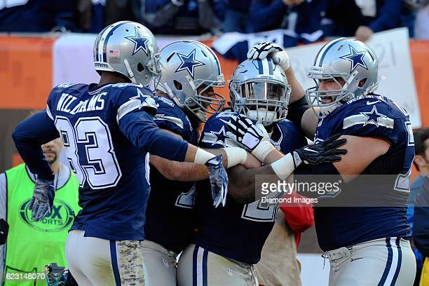 Running back Ezekiel Elliott of the Dallas Cowboys celebrates a touchdown with center Travis Frederick right guard Zack Martin and wide receiver...