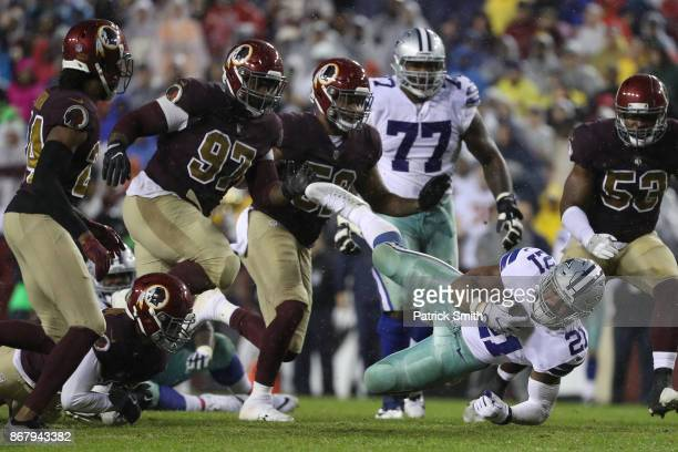 Running back Ezekiel Elliott of the Dallas Cowboys get tackled by strong safety Montae Nicholson of the Washington Redskins during the third quarter...
