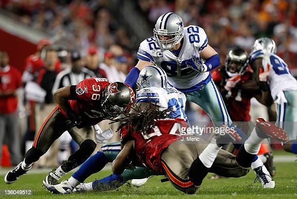 Running back Felix Jones of the Dallas Cowboys is tackled by defenders Tanard Jackson and Adrian Clayborn of the Tampa Bay Buccaneers during the game...