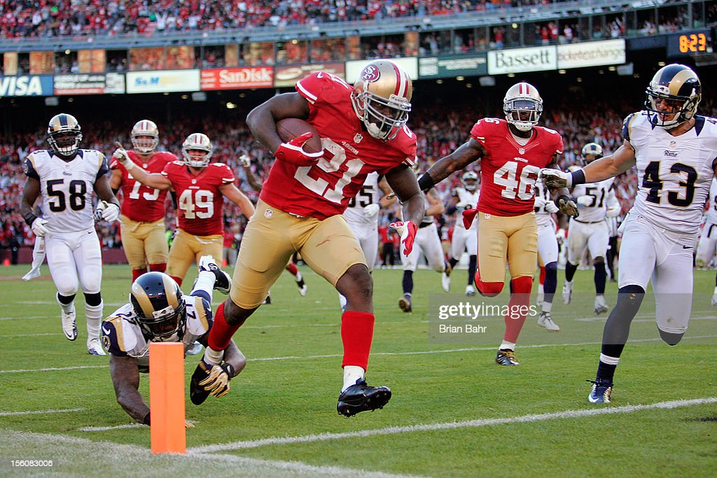 Running back <a gi-track='captionPersonalityLinkClicked' href=/galleries/search?phrase=Frank+Gore&family=editorial&specificpeople=233698 ng-click='$event.stopPropagation()'>Frank Gore</a> #21 of the San Francisco 49ers scores a touchdown on a 20-yard run past safety <a gi-track='captionPersonalityLinkClicked' href=/galleries/search?phrase=Quintin+Mikell&family=editorial&specificpeople=763498 ng-click='$event.stopPropagation()'>Quintin Mikell</a> #27 of the St. Louis Rams in the fourth quarter on November 11, 2012 at Candlestick Park in San Francisco, California. The teams tied 24-24 in overtime.