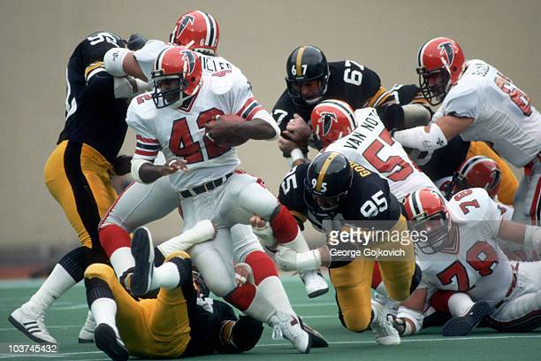Running back Gerald Riggs of the Atlanta Falcons attempts to escape the grasp of defensive lineman John Goodman of the Pittsburgh Steelers as Jeff...