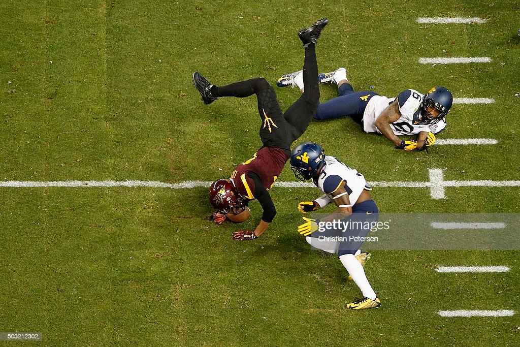 Running back Gump Hayes of the Arizona State Sun Devils is tackled by cornerback Ricky Rumph and safety Dravon AskewHenry of the West Virginia...