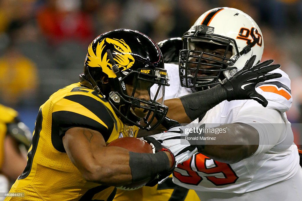 Running back Henry Josey #20 of the Missouri Tigers runs against Calvin Barnett #99 of the Oklahoma State Cowboys in the first half during the AT&T Cotton Bowl on January 3, 2014 in Arlington, Texas.