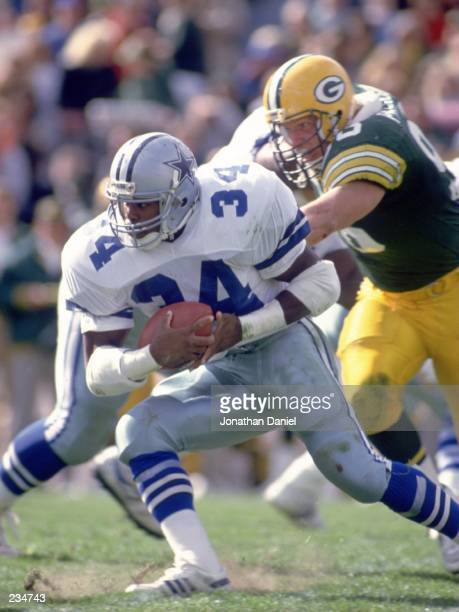 Running back Herschel Walker of the Dallas Cowboys makes a cut up field to avoid the pursuing defense of the Green Bay Packers during the Cowboys...