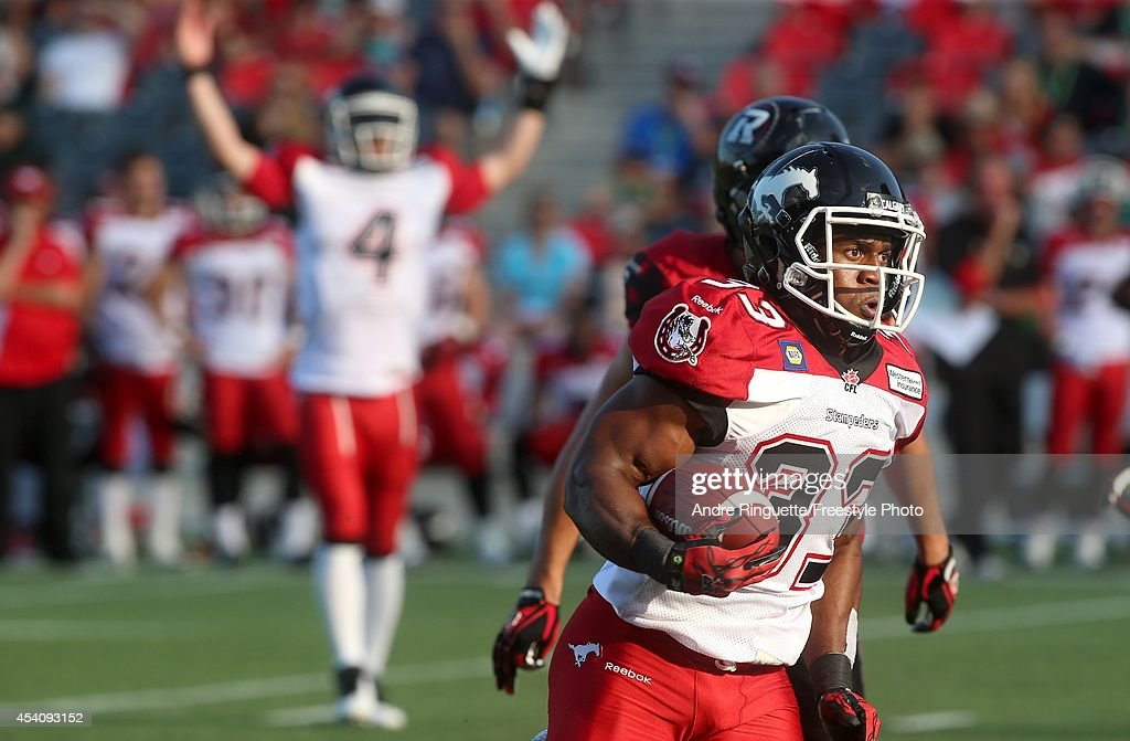 Running back Hugh Charles #33 of the Calgary Stampeders rushes for a fourth quarter touchdown against the Ottawa Redblacks during a CFL game at TD Place Stadium on August 24, 2014 in Ottawa, Ontario, Canada.