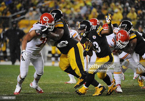 Running back Isaac Redman of the Pittsburgh Steelers runs with the football as offensive linemen Willie Colon and Ramon Foster block defensive end...