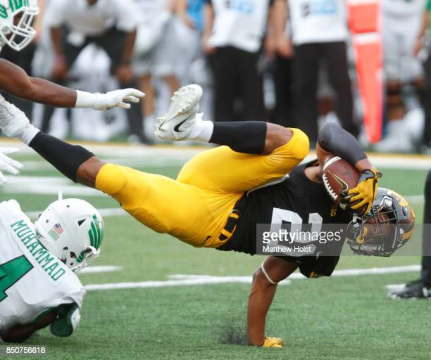 Running back Ivory KellyMartin of the Iowa Hawkeyes is tripped up during the fourth quarter by safety Khairi Muhammad of the North Texas Mean Green...