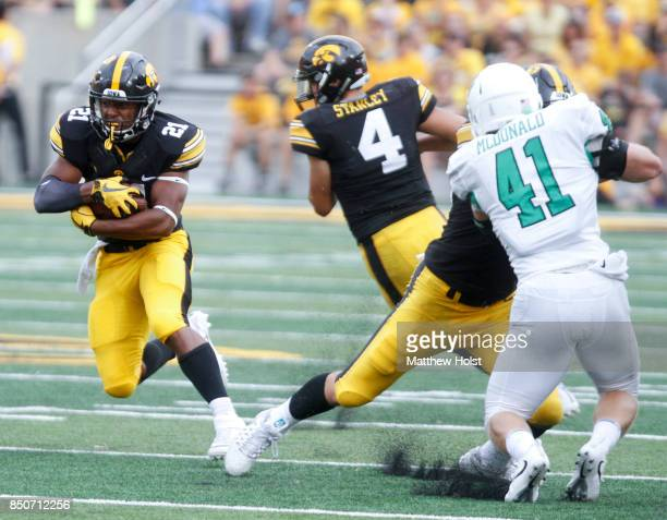 Running back Ivory KellyMartin of the Iowa Hawkeyes runs up the field during the third quarter in front of linebacker Colton McDonald of the North...