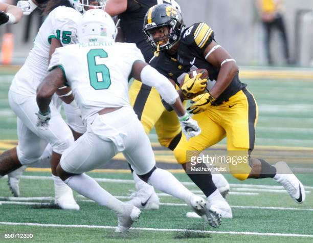 Running back Ivory KellyMartin of the Iowa Hawkeyes runs up the field during the third quarter in front of safety Kishawn McClain of the North Texas...
