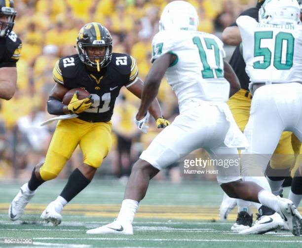 Running back Ivory KellyMartin of the Iowa Hawkeyes runs up the field during the third quarter in front of linebacker Joshua Ozougwu of the North...