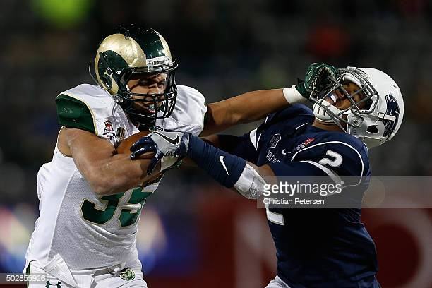 Running back Izzy Matthews of the Colorado State Rams stiff arms defensive back Asauni Rufus of the Nevada Wolf Pack as he rushes the football during...