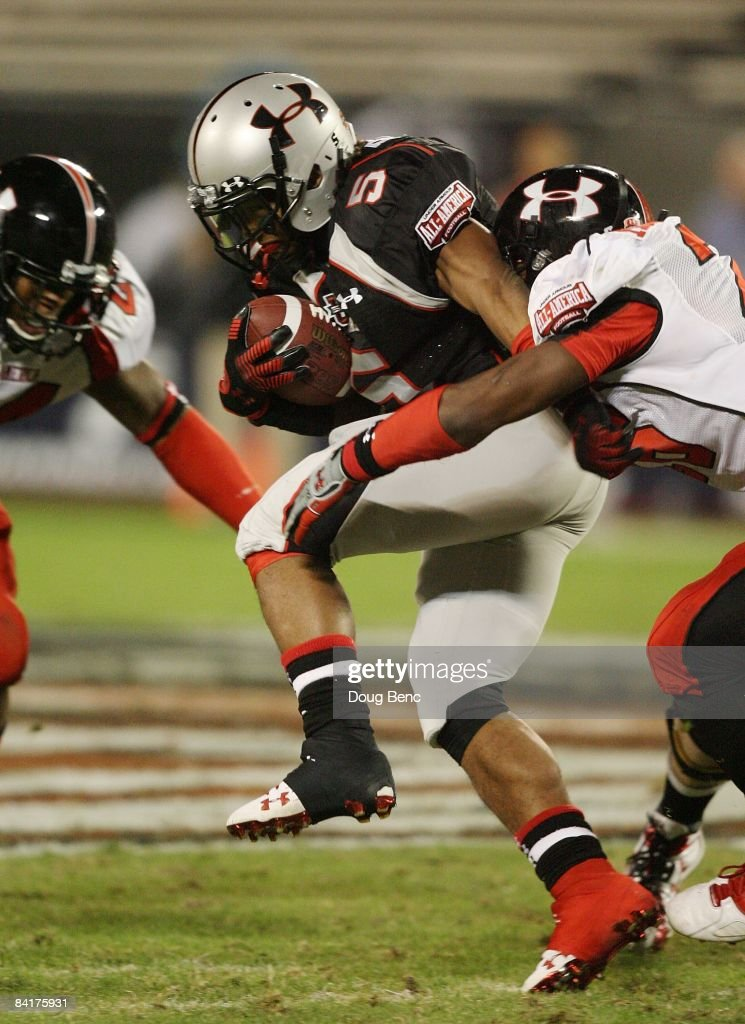 Running back Jaamal Berry of the black team is brought down before fumbling in the All America Under Armour Football Game at Florida Citrus Bowl on...
