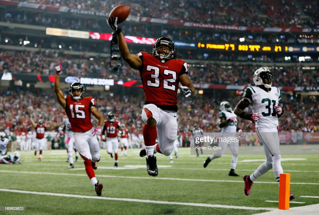 Running back <a gi-track='captionPersonalityLinkClicked' href=/galleries/search?phrase=Jacquizz+Rodgers&family=editorial&specificpeople=5518956 ng-click='$event.stopPropagation()'>Jacquizz Rodgers</a> #32 of the Atlanta Falcons scores his second touchdown of the game against the New York Jets during their game at the Georgia Dome on October 7, 2013 in Atlanta, Georgia.